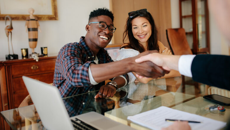 Happy property owners shaking hands with real estate broker after a deal.